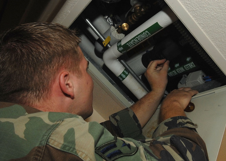 Airman 1st Class Cody Stockman, 355th Engineer Squadron, checks an air conditioner for condensation on July 25.  Airman Stockman is an heating, ventiliation and air conditing apprentice for CES. (US Air Force Photo By:  Senior Airman Jacqueline Romero)
