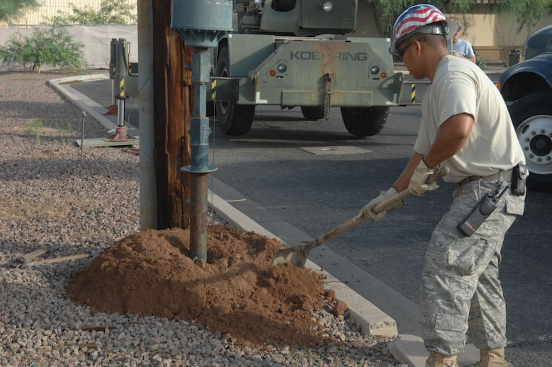 Staff Sgt. Carlo Mangoba, 355th Civil Engineer Squadron, tries to keep some of the dirt out new hole that the new pole will do in on July 26.  Sergeant Mangoba is and electrical journeyman for CES.  (US Air Force Photo By:  Senior Airman Jacqueline Romero)
