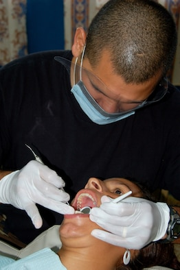 Staff Sgt. Juan Gutierrez, a bilingual dental technician from the 42nd Medical Group deployed to Medical Readiness Training Exercise Panama, cleans a patient's teeth at a school in Pesé, Panama, Monday. (Air Force photo by Capt. Ben Sakrisson)
