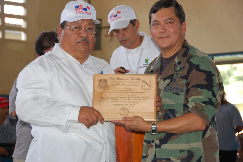 United States Air Force Lt. Col. Joseph A. Lopez, the Medical Readiness Training Exercise Panama Mission Commander from Maxwell Air Force Base, Ala., presents a plaque to Dr. Gonzales the director of the Panama Regional Ministry of Health during closing ceremonies for the MEDRETE July 24  in Pesè, Panama. The MEDRETE is a two-week long U.S. Southern Command sponsored medical exercise designed to hone the skills of medical personnel while providing free health care in remote locations through partnership with host nation doctors.