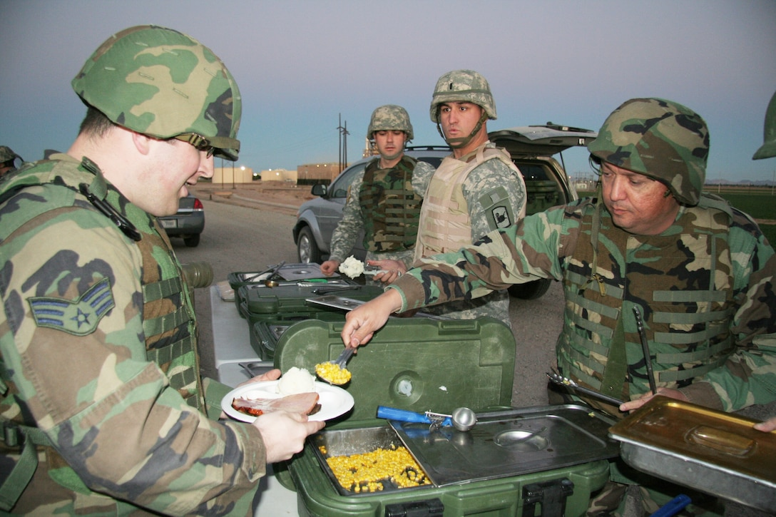 Chaplain (Maj.) Mike Martinez (right) serves a hot meal on Christmas Eve to an Airman assigned to an entrance identification team in Yuma, Ariz., as part of Operation Jump Start. (Army National Guard photo by Sgt.Ed Balaban)