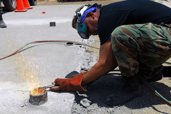 Causing some sparks to fly, Staff Sgt. Marvin Williams of the 149th Fighter Wing Civil Engineer Squadron blow-torches a pipe level with the concrete surface of a water crossing. The unit worked on real-world engineering projects  while simultaneously completing two weeks of training.