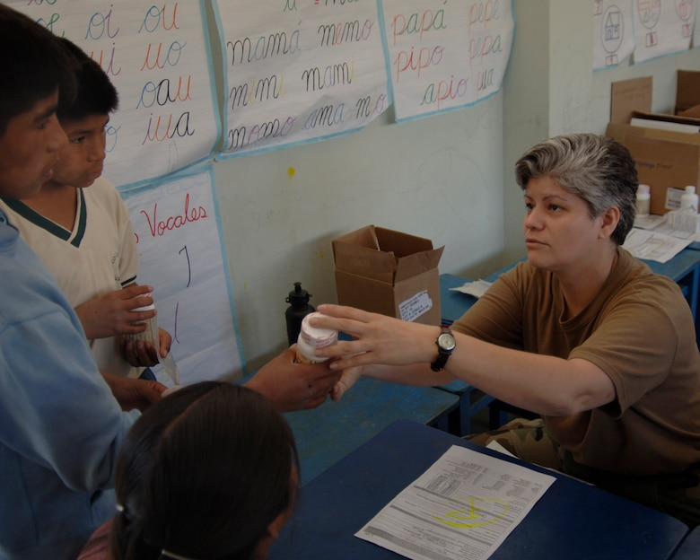 Hospital Corpsman 3rd Class Luz Ortega, from Operational Health Support Unit - Great Lakes, Ill., gives a bottle of multi-vitamins to a Peruvian patient at the pharmacy during a medical mission in Cobadonga, Peru, July 26.  Navy medics are deployed to Ayacucho, Peru to support three medical missions during New Horizons - Peru 2008, a humanitarian mission set on bringing relief to underpriviliged Peruvians. (U.S. Air Force photo/1st Lt. Mary Pekas)