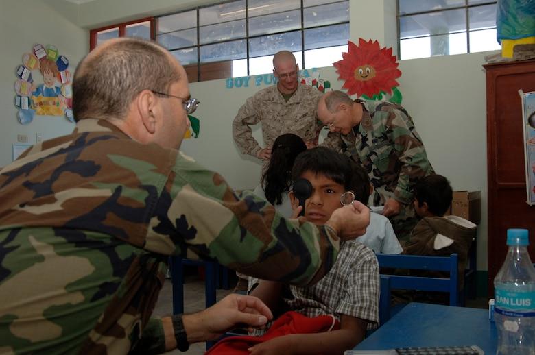 Navy Dr. (Cmdr.) Michael Radoiu, an optometrist with Task Force New Horizons, performs an eye examination on a Peruvian boy during a medical mission in Cobadonga, Peru, July 26.  Medical professionals from Opeational Health Support Unit - Great Lakes, Ill., are deployed to Peru to support New Horizons - Peru 2008, a partnered U.S. and Peruvian effort to bring humanitarian aid to the people of Ayacucho, Peru.  (U.S. Air Force photo/1st Lt. Mary Pekas)