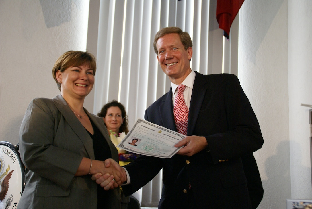 Zita Chouchan, the first military spouse to become a naturalized U.S. citizen overseas, accepts congratulations from Jonathan Scharfen, acting director of U.S. Citizenship and Immigration Services, and Kristina Carty-Pratt, director of the USCIS field office in Frankfurt, Germany, May 29, 2008. Photo courtesy of U.S. Citizenship and Immigration Services