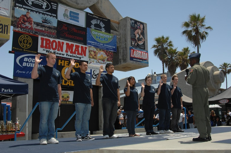 Seven Delayed Entry Program Recruits entering the Air Force receive the oath of office from Col. Kenneth Allison, chief of the concept development division at the Muscle Beach International Classic, May 26.  The recruits from left to right are:  Michael Edwards, Thai Thach, Andelson Tocong, Vivian Ortiz, Jennifer Kuehn, Thomas Arzola, and Chris Webb. (Photo by Lou Hernandez)