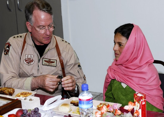 Lt. Gen. John Bradley unclasps a watch for Lamia, a 10-year-old Afghan girl he met last winter during a humanitarian aid drop to her village. Bradley's wife, Jan, spearheaded a donation drive that collected several boxes of supplies for Lamia and her village of Shakal. General Bradley is the Air Force Reserve Command commander. (U.S. Air Force photo/Capt. Toni Tones)