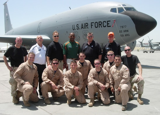 """Four of the Airmen who recently helped fly five college football coaches to Southeast Asia were from the 931st Air Refueling Group.  The coaches (back row from left to right) included's Yale's Jack Siedlecki (with white shirt), Georgia's Mark Richt, Miami's Randy Shannon, Notre Dame's Charlie Weis, and Auburn's Tommy Tuberville (with orange hat). With Richt's hand on his shoulder is pilot and Atlanta, Ga., native Capt. Eric Junkins.  On the far left is Staff Sgt. Jon Barber (w black t-shirt), 931st Maintenance Squadron crew chief. Kneeling directly in front of Tuberville is Tech. Sgt. Chris Norris, boom operator, and in front of Norris is pilot Capt. Keith """"Kip"""" Anderson (with sunglasses).  Captain Junkins, Captain Anderson and Sergeant Norris are members of the 18th Air Refueling Squadron, the flying squadron of the 931st ARG."""