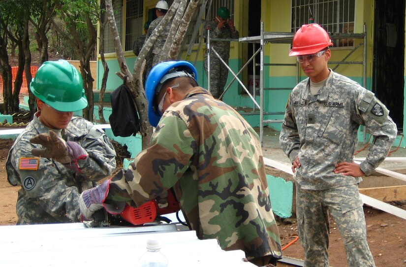 SOTO CANO AIR BASE, Honduras--United States Military Academy cadet Walter Arevalo observers U.S.soldier and a Honduran soldier working at a school renovation site in Honduras during his visit here as part of Academy?s Academic Individual Advanced Development, a program similar to summer internships in whichengineering cadets gain valuable, real-world experience. (U.S. Army photo by Cadet 2nd Class Ryan Kim)
