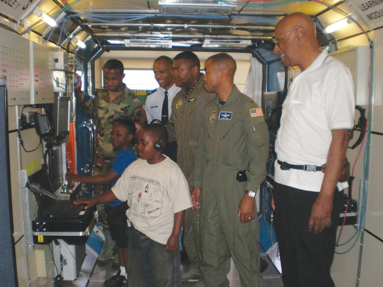 Students get a hands-on technology demo with the assistance of Lt Col Ivan Thompson, Maj Jermaine Brinson, Maj Rico Jones, Lt Rashim McKinney, and Hal Walker Jr., co-founder, African-American Male Achievers Network (A-MAN), Inc. International Science Discovery and Learning Center in Inglewood, California.  (photo by Terita R. Norton, Aerospace Corporation)