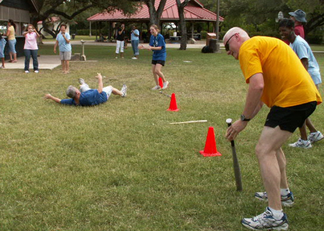 Col. Bill Foote (left), personnel services director, and Chief Master Sgt. Andy Kaiser (right), command chief, both from the Air Force Personnel Center here at Randolph Air Force Base, Texas, attempt to run a straight line after 10 rotations with their foreheads on a bat during AFPC's sports day. Dizzy bat was just one of several untraditional events. (US Air Force photo/Master Sgt. Kat Bailey)