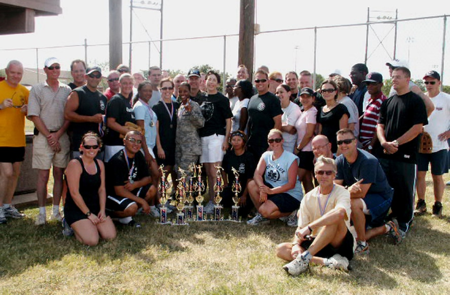 Chief Master Sgt. Andy Kaiser, Air Force Personnel Center command chief (far left) and Rob Thomas, AFPC executive director (seated, right front), pose with AFPC's sports day champion directorate, assignments. AFPC held the sports day here at Randolph Air Force Base, Texas, to boost esprit de corps and camaraderie. (US Air Force photo/Master Sgt. Kat Bailey)