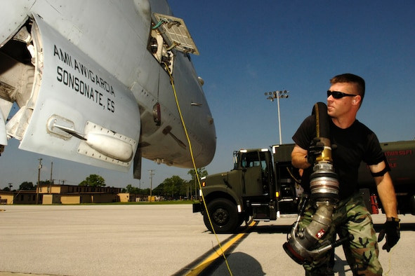 SCOTT AIR FORCE BASE, Ill. -- Staff Sgt. Ed Mueller, 375th Logistics Readiness Squadron, Fuels Management Flight, distribution operator, pulls hose from his fuel truck to a waiting fighter jets that stopped at Scott last week. (US Air Force photo/ Airman First Class Megan Gilliland)