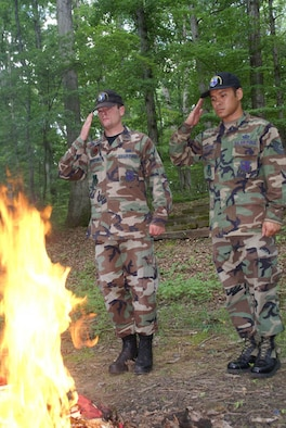 From left, 1st Lieutenant Robert Thornton and Tech. Sgt. John Bankston, with AEDC's Air Force Honor Guard, salute an American flag while it burns during a flag retirement ceremony held at Camp Arrowhead, a Boy Scout camp on the base near Woods Reservoir. (Photo by Philip Lorenz III)