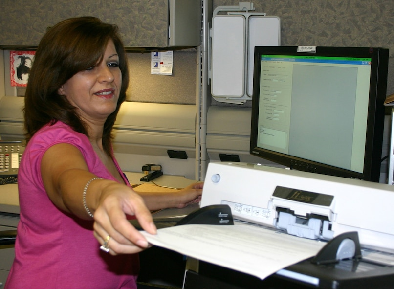 Blanca Rubio, a contract scanning team leader at the Air Force Personnel Center here, scans the last paper unit personnel record June 3.   Since September 2006, AFPC has scanned about 325,000 records that were shipped to AFPC's Master Personnel Records Branch from every active-duty base in the Air Force. The paper to electronic records transition is part of the Air Force's ongoing commitment to Personnel Services Delivery Transformation. (U.S. Air Force photo/Richard Salomon)