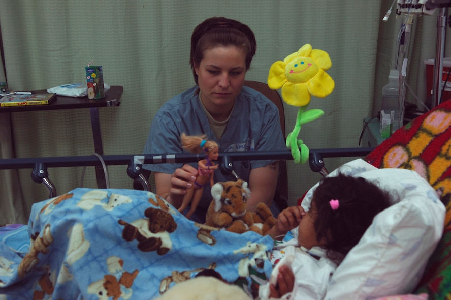 BALAD AIR BASE, Iraq -- Senior Airman Nicole Vaughn, assigned to the 23rd Expeditionary Fighter Squadron, spends time with a young Iraqi girl, a patient at the Air Force Theater Hospital here, as part of a job swap program. The program allows Airmen outside of the medical career field to spend a day shadowing hospital personnel. Airman Vaughn is deployed from Spangdahlem Air Base, Germany. (U.S. Air Force photo /Staff Sgt. Mareshah Haynes)