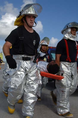 U.S. Air Force Senior Airman Mathew Derheim carries a victim to safety at this years Full Scale Disaster Drill Exercise at Guam International Airport on June 6, 2008. Andersen AFB Fire Rescue Team was one of several Departments that helped out with this disaster exercise. (U.S. Air Force photo by Airman 1st Class Courtney Witt)