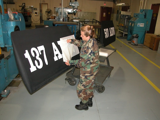 Staff Sgt. Sue Hathaway, a structural repair and corrosion control technician with the Air Force Reserve's 507th Air Refueling Wing, peels away transfer paper backing while applying new lettering to a KC-135 ruddervator.     As a result of the 2005 BRAC process, the 507th Air Refueling Wing became the first Air Force Reserve wing to become host to an Air National Guard wing.     The Oklahoma Air National Guard's 137th Air Refueling Wing began flying associate missions here at Tinker Air Force base earlier this year.   Assigning dual wing identification on the KC-135 ruddervator is part of local processes to provide identification and partnership parity.