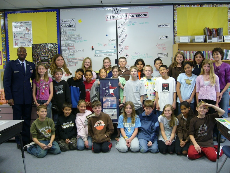 """CANNON AIR FORCE BASE, N.M. - Capt. Tyler Moore, 27th Special Operations Wing Equal Opportunity director, stands with Debra Dale's fifth-grade class at Eyestone Elementary School in Wellington, Colo. The students wrote letters to Captain Moore while he was deployed and he then published a book compiled of the letters titled """"Dear Captain Moore."""" (courtesy photo)"""