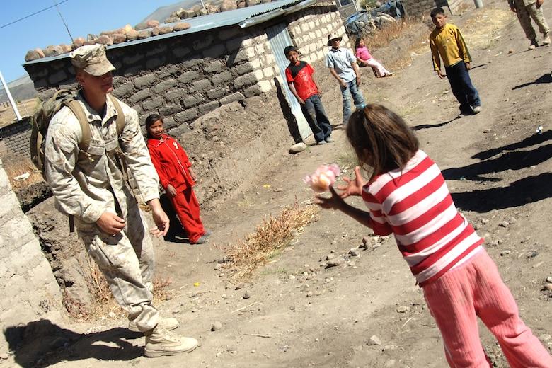 U.S. Marine Sgt. Allan Parvis, plays a game of catch, June 7, with five Peruvian children during a visit to Yanama, Peru. U.S. servicemembers are in Peru participating in New Horizons-Peru 2008, a U.S. Southern Command-sponsored humanitarian set on improving the lives of underprivileged Peruvians.