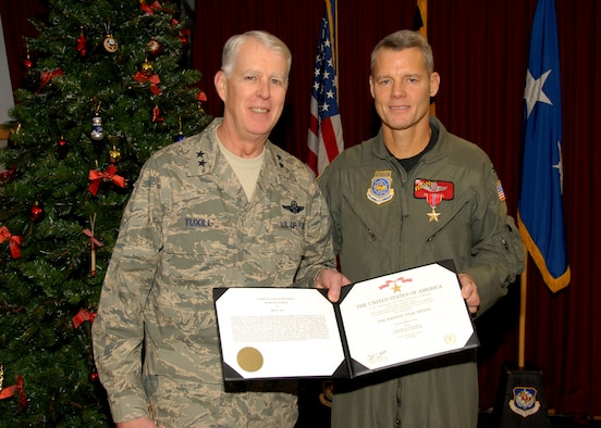 Maj. Gen. Bruce F. Tuxill presents the Bronze Star to Col. Brian Neal (U.S. Air Force Photo by Master Sgt. Ed Bard)
