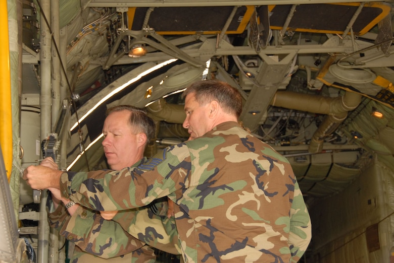 Chief Master Sgt. Phillip Tavenier and Master Sgt. William Davis adjust the cargo door on the C-130 during their feild training class. The 107th is converting from the KC-135R to the C-130H2. (U.S. Air Force photo/Senior Master Sgt. Ray Lloyd).