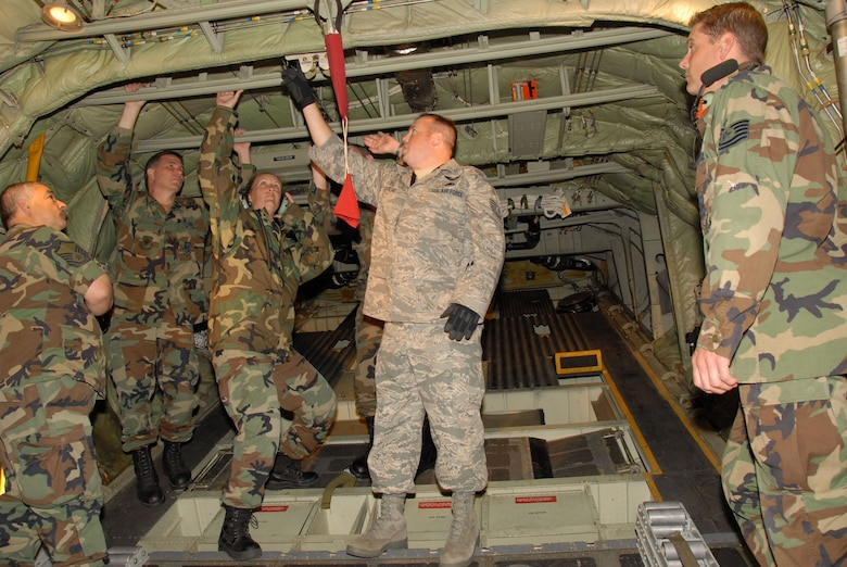 Tech. Sgt. Tim Dodge of the AETC Field Training Team explains the cargo door operation. Members of the 107th Maintenance Squadron perform field training on the C-130H2 aircraft at the Niagara Falls Reserve Station . Standing behind the instuctor from left to right, Master Sgt. Carl Azzarelli, Master Sgt. William Davis, Master Sgt. Nancy Traxler and Tech. Sgt. Mark Traxler looks on from the right. The 107th is converting from the KC-135R to the C-130H2.(US Air Force Photo/ Senior Master Sgt Raymond Lloyd)