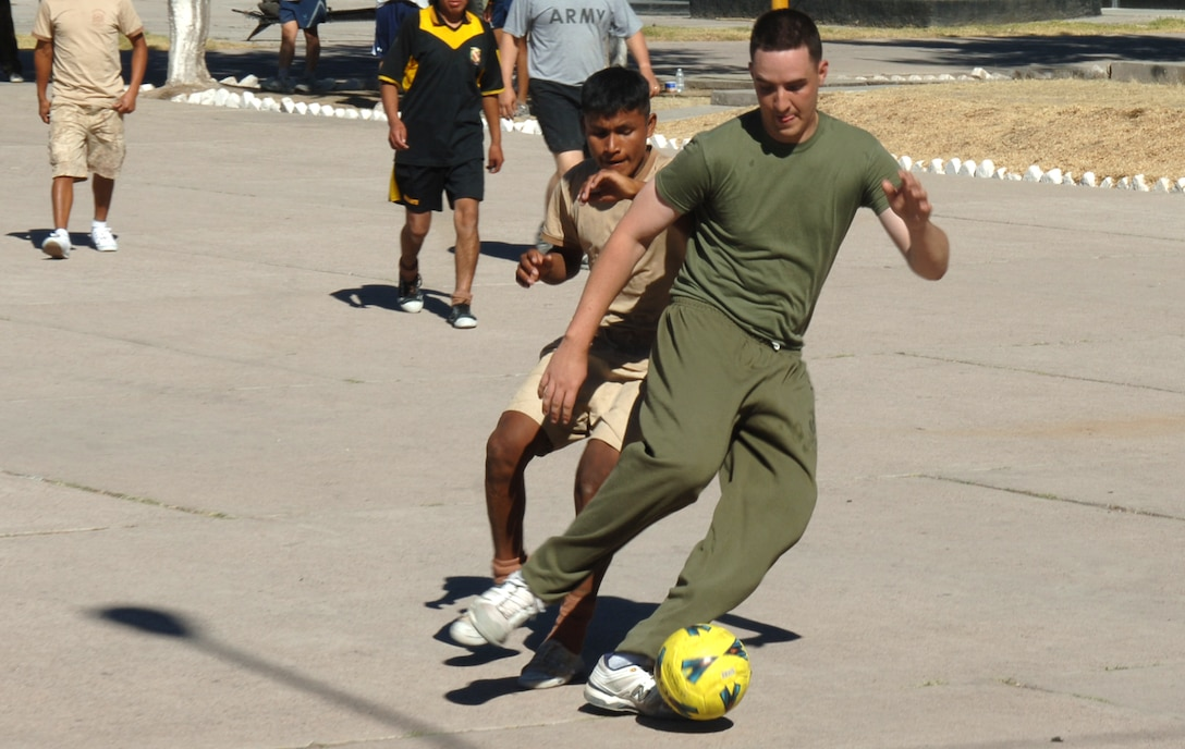U.S. Marine Lance Cpl. Matthew Carroll, assigned to Task Force New Horizons, dribbles a ball around a Peruvian soldier, June 8 , in a soccer game between the U.S. and Peruvian militaries during New Horizons Peru 2008, a U.S. and Peruvian effort to bring relief to underprivileged Peruvians.  (U.S. Air Force photo/Tech. Sgt. Kerry Jackson)