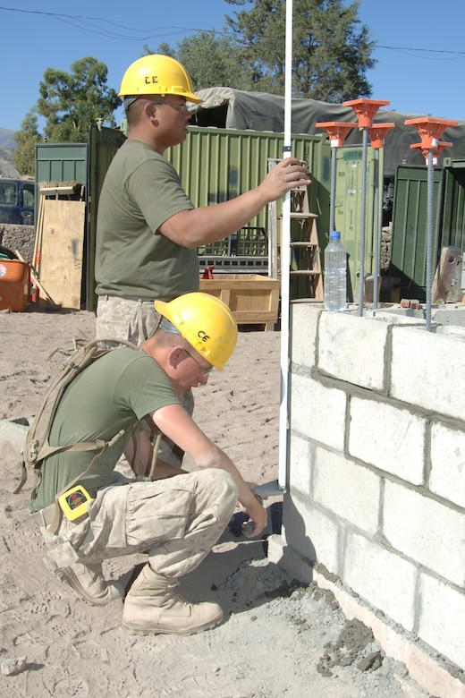 U.S. Marine Lance Cpls. Michael Zukowski and Angelo Acevedo, assigned to Westover Air Reserve Base, Mass., level cemement blocks, June 6, for the construction of a clinic in Yanamilla, Peru in support of New Horizons Peru - 2008, a U.S. and Peruvian humanitarian mission set on improving the quality of life for underpriviledge Peruvians. (U.S. Air Force Photo/ Tech. Sgt. Kerry Jackson)
