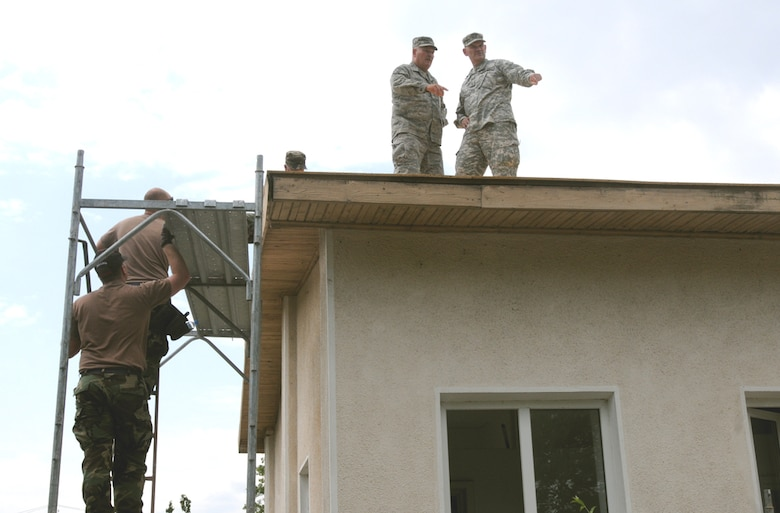 The North Dakota Adjutant General, Maj. Gen. David A. Sprynczynatyk (right), and Command Chief Master Sgt. Brad Childs, the 119th Wing command chief, get an eagle's eye view of the construction site during their visit June 6 to the 119th Civil Engineering Squadron's worksite in Romania. (Photo by Sgt. Maj. Kimberly Williams)