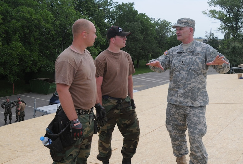 The North Dakota Adjutant General, Maj. Gen. David A. Sprynczynatyk (right), took to the roof to talk with Senior Airman Austin Roller (left) and Senior Airman Jared Kuhn, both with the 119th Civil Engineering Squadron.  The Airmen are currently deployed to Romania as part of Joint Task Force-East. (Photo by Sgt. Maj. Kimberly Williams)