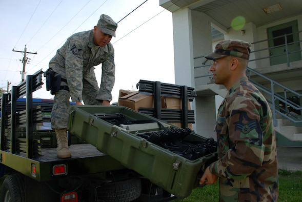 Tech. Sgt. Mark Sanchez, 11th Security Forces Squadron, craftsman instructor and Senior Airman Max Andrade, 69th Arial Port Squadron, cargo journeyman, load weapons into a vehicle during a training exercise at Fort A.P. Hill, Va. Saturday. (U.S. Air Force photo/Senior Airman Ashley Crawford)