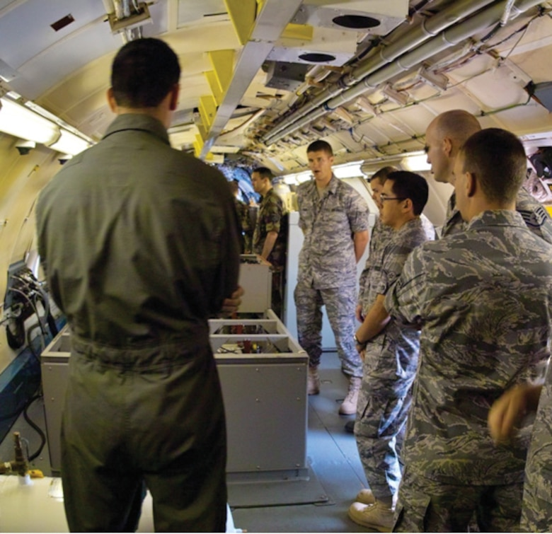 Special equipment operator (in training) Staff Sgt. Stephen Carpenter, left, briefs SPINSTRA students from Goodfellow Air Force Base on the Whole Air Collection System, one of several collectors onboard the WC-135 Constant Phoenix aircraft. (U.S. Air Force photo by Master Sgt. Steven Clark)