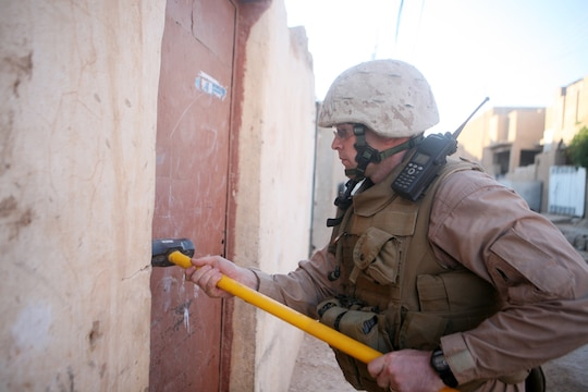 Gunnery Sgt. Daniel T. Jones, a platoon sergeant with Mike Battery, 14th Marine Regiment, 2nd Light Armored Reconnaissance Battalion, Regimental Combat Team 5, hammers a door to a storage space during a cache search in Rutbah, Iraq, June 20. Although the city of Rutbah has become safer, the insurgency is still out there and the Marines with the Chattanooga, Tenn., based unit will be there to there to find them.::r::::n::