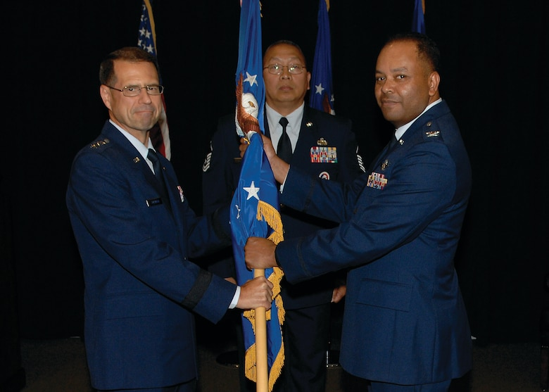 Col. Samuel Greaves accepts the SMC/Military Satellite Communications Wing guidon from AFSPC/SMC Commander, Lt. Gen. John T. 'Tom' Sheridan signifying his acceptance of command as the new commander of Space and Missile Systems Center Military Satellite Communications Wing. Colonel Greaves  was formerly commander of the SMC Launch and Range Systems Wing. (photo by Stephen Schester)