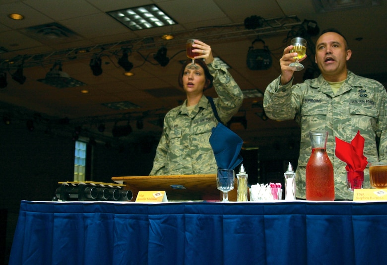 "Technical Sergeant Jennifer Maitland, mess vice president, and Tech. Sgt. Stephen Burrows, the sergeant-at-arms, raise a toast ""to the President of the United States!"" at the 17th Training Wing Joint Enlisted Dining-In June 12. (U.S. Air Force photo by Senior Airman Stephen Musal)"