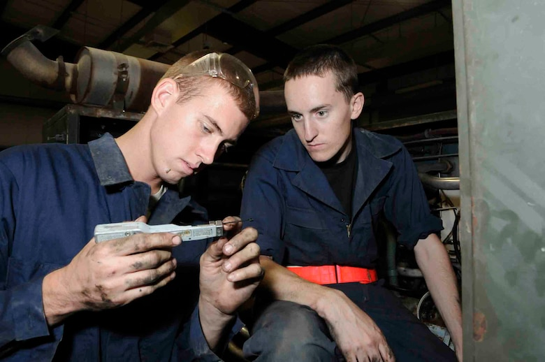 SOUTHWEST ASIA -- Senior Airman Anthony Dodge function checks a zip tie cutter while Airman 1st Class Lucas Lemoine prepares to use it to secure chaffe wrap on hydraulic test stand hoses at a Southwest Asia air base June 18.  Due to the intense heat and mechanical vibrations on the hydraulic test stand wrapping has to be secured to prevent it from coming off.  Both are assigned to 379th Expeditionary Maintenance Squadron. Airman Dodge is deployed from MacDill Air Force Base, Fla. and Airman Lemoine is deployed from Offutt Air Force Base, Neb.  (U.S. Air Force photo/Tech. Sgt. Johnny Saldivar)