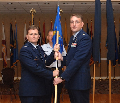 Colonel Jeff Dunn, 14th Flying Training Wing interim wing commander, presents Maj. Paul Porter with the new 14th Contracting and Comptroller Squadron (Provisional) guidon June 24 at the Columbus Club. Major Porter assumed command of the newly established 14th CONS-CPTS (P) during the ceremony. (U.S. Air Force photo by Airman Josh Harbin)