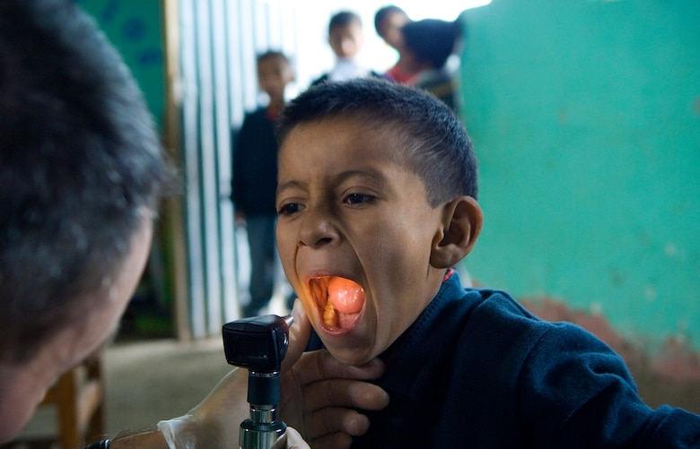 Maj. Eric Potwardowski checks the tonsils of a Peruvian child during free medical examinations June 22 inside a local school house in Ayacucho, Peru. American servicemembers are providing medical care during New Horizons-Peru 2008, a U.S. and Peruvian partnered humanitarian mission set on providing relief to underprivileged Peruvians. Major Potwardowski is deployed from the 452nd Medical Squadron at March Air Reserve Base, Calif. (U.S. Air Force photo/Staff Sgt. Bennie J. Davis III)