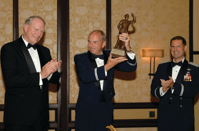Retired Lt. Gen. Michael A. Hamel, former SMC commander, holds up his newly awarded General Bernard A. Schriever, National Space Leadership statue, along with another presenters, retired Lt. Gen. Brian Arnold, former SMC commander and Lt. Gen. John T. Sheridan, current SMC Commander, during the AFA Salute to SMC banquet, June 20. (Photo by Stephen D. Schester)