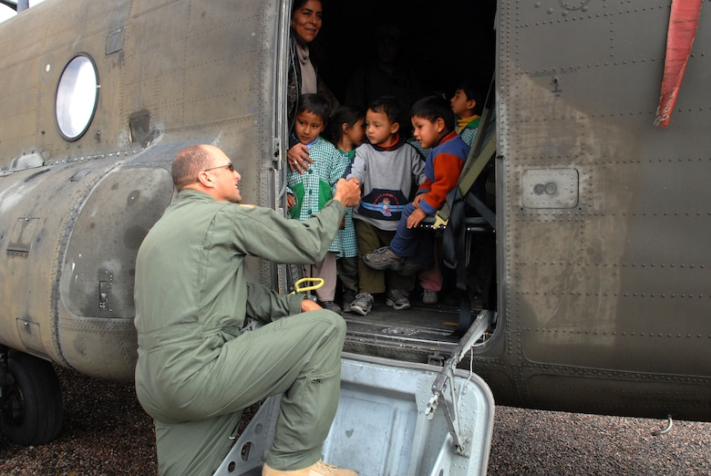U.S. Army Sgt. Larry Botkins, a helicopter engineer currently assigned to Task Force New Horizons- Peru 2008, greets the children of I.E. Inicial CRL. Miguel Peñarrieta Elementary School in Los Cabitos, Peru, during their tour of a U.S. CH-47 Chinook helicopter currently assigned to Task Force New Horizons and residing in Los Cabitos, Peru. (U.S. Air Force photo/Tech. Sgt. Kerry Jackson)
