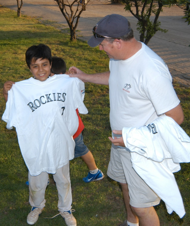 Airmen assigned to Davis-Monthan Air Force Base, Ariz., hand out Colorado Rockies tee shirts and backpacks to the children of Santiago, Chile. The Airmen and U.S. Air Force aircraft were part of FIDAE 2008, one of the largest combined air and trade shows, and for Exercise Newen 2008. The exercise builds the partnership between the U.S. and Chilean militaries. U.S. Airmen got to practice baseball diplomacy as well, in a friendly game that matched them up to the Santiago Metros, a 19-and-under squad filled with semi-pros. The Colorado Rockies donated items for the children, and the Air Force gave away memorabilia, as well as the game, to their opponents. (U.S. Air Force photo/Master Sgt. Jason Tudor)