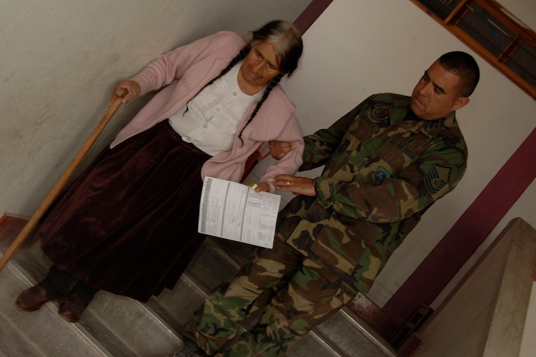 U.S.  Air Force Master Sgt.  Javier Retamoza, a medical technician assigned to Task Force New Horizons, assisted an elderly Peruvian woman down the stairs, June 26, after she was treated by U.S.  Air Force medical doctors supporting New Horizons Peru, a U.S. and Peruvian partnered humanitarian mission set on providing relief to underprivileged Peruvians. (U.S. Air Force photo/ by Tech. Sgt. Kerry Jackson)