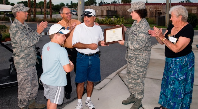 Project Emeritus volunteer Lou Dalmau (center in white shirt) receives a plaque from 45th Space Wing Commander Susan Helms Tuesday morning at the Manatee Cove Golf Course. A retired Air Force technical sergeant, Mr. Dalmau has accumulated more than 3,000 volunteer hours ferrying customers around the course in the shuttle golf cart he operates. (U.S. Air Force photo by Jim Laviska).