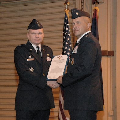 U.S. Air Force Presiding Officer Col. Mark Talley presents Lt. Col. Peter Ridilla  the Meritorious Service Medal during the 36th Civil Engineer Squadron Change of Command Ceremony here June 30. Lieutenant Colonel Ridilla has been the Commander of the 36th Civil Engineer Squadron for the past two years and now relinquishes his command to Lieutenant Colonel Richard Mathews. (U.S. Air Force photo by Airman 1st Class Courtney Witt)