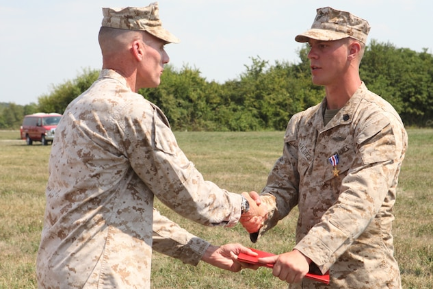 Maj. Gen. James M. Lariviere, former commanding general for the 4th Marine Division, congratulates Staff Sgt. Alec Haralovich, after presenting him the Silver Star Medal, the nation?s third highest award for combat valor. After Haralovich was shot twice in his body armor by an insurgent, he destroyed an enemy stronghold with a rocket and led his Marines on a two-hour assault after their ambushers during an Afghanistan deployment in 2011. Haralovich is a reconnaissance Marine assigned to E Company, 4th Reconnaissance Bn., 4th Marine Division.