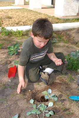 Toby Mills, 5, displays his gardening skills at the Randolph Child Development Center.