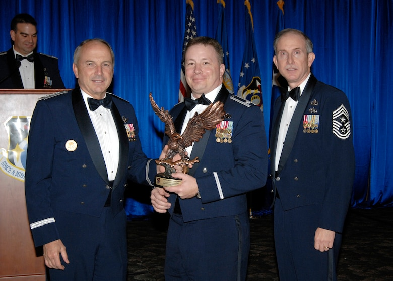 Lt. Col. Brett Scrum accepted the Noncommissioned Officer of the Year Staff Award on behalf of Staff Sgt Dreamy Peckhem, who is currently deployed. Also pictured is SMC Commander Lt. Gen.  Michael Hamel and SMC Command Chief Master Sergeant Steven Crocker. (Photo by Lou Hernandez)
