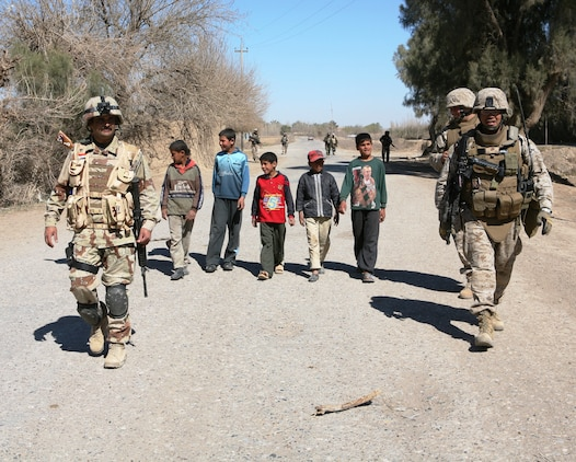 Maj. John E. Orille, (right), 2nd Battalion, 3rd Brigade, 1st Iraqi Army Division Military Transition Team senior adviser, and 1st Lt. Khalid Shihab Ahmed al-Alwani, 2nd Company, 2nd Battalion company commander, conduct a presence patrol in the town of Hembis, Iraq.  A group of Iraqi children joined the patrol as it entered the town.  Patrols like these allow the Iraqi Army to interact directly with the local populace, building trust and relationships that can lead to information on enemy activity in the future.  MiTT members accompany these patrols, but all of the planning and execution are done by the Iraqis.