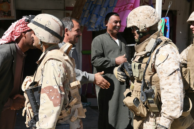 Maj. John E. Orille, (right), 2nd Battalion, 3rd Brigade, 1st Iraqi Army Division Military Transition Team senior adviser, and 1st Lt. Khalid Shihab Ahmed al-Alwani, 2nd Company, 2nd Battalion company commander, greet local men while conducting a presence patrol in the town of Hembis, Iraq.  Al-Alwani uses these patrols as an opportunity to talk to local leaders and members of the Sons of Iraq to gather information on possible enemy activity and build trust with the local population. The 2nd Battalion has been patrolling aggressively in the Diyala River Valley since January in an effort to clear Al Qaeda in Iraq and other terrorist groups from the area.